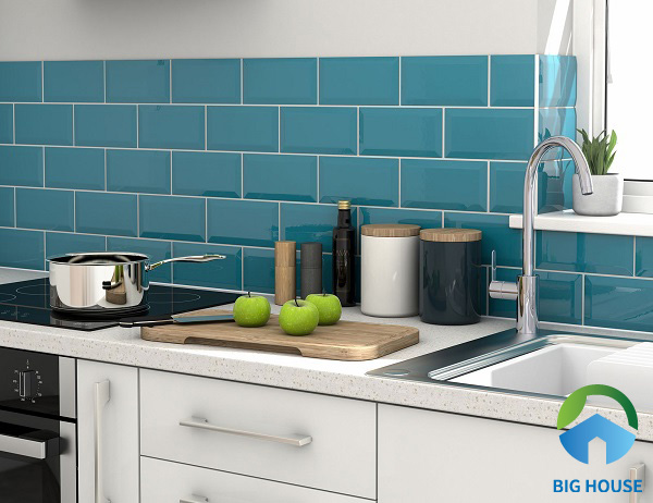 Những viên gạch thẻ xanh dương bề mặt bóng kết hợp nội thất bếp màu trắng giúp không gian bếp bừng sáng